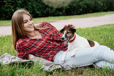 endear: Smiling pretty 20-25 years girl in tartan red shirt with long hair lies on the grass with her active foxterrier. side view