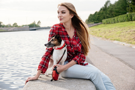 Nice pretty long haired girl in tartan red shirt sit at the river embankment with smiling fox-terrier. Look at the side