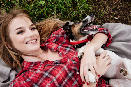 Smiling pretty 20-25 years girl in tartan red shirt with long hair lies on the grass with her active foxterrier. Top view. Standard-Bild