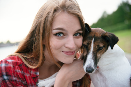 Pretty girl fooling around with her small pet outdoor. Close up portrait Standard-Bild