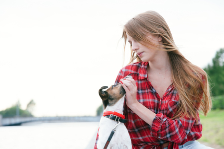 Nice pretty long haired girl in tartan red shirt sit at the river embankment, and play with fox-terrier. Looking each other. Standard-Bild