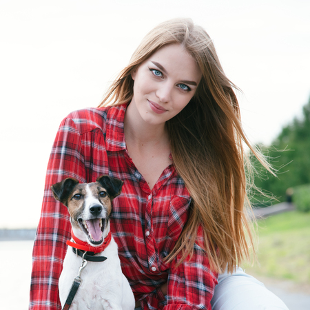 Nice pretty long haired girl in tartan red shirt sit at the river embankment with smiling fox-terrier. Look at camera.