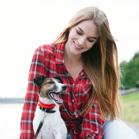Nice pretty long haired girl in tartan red shirt sit at the river embankment with smiling fox-terrier. Look each other. Standard-Bild