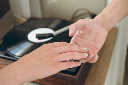 man tenderly keep his girlfriends hand in front of vinyl player Stock Photo