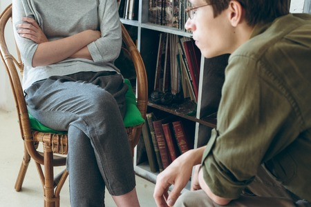 family conflict. Couple discussing sitting near bookshelves. Modern casual hipster look. Standard-Bild