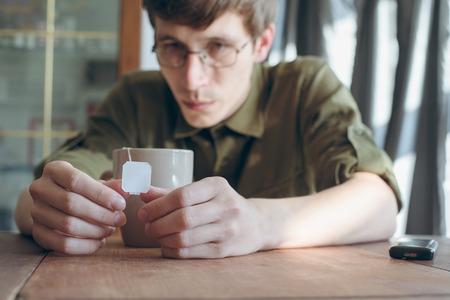 sad man drinking tea on the wooden table