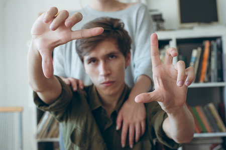 young man makes frame gesture and his girl stand beside him. focus on hands.