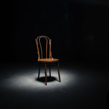 Lonely chair in the spot of light on black background at empty room Фото со стока
