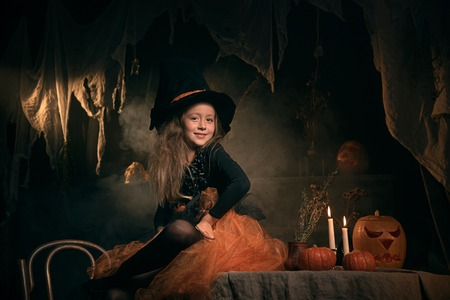 small girl in witch costume sit on the table in halloween decorations