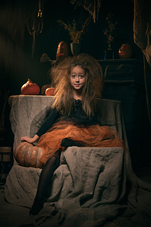 small girl in witch costume sit on Halloween decoration