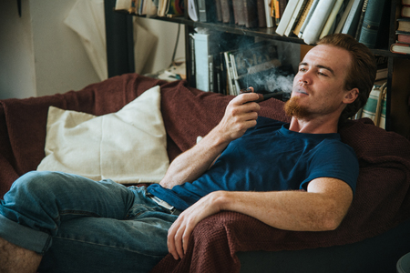 young man rest at the sofa and smoke pipe
