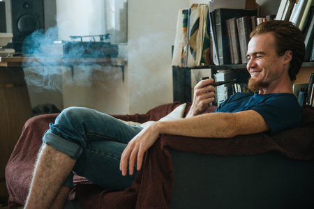 Smiling young man smoke pipe, listen old music and enjoy his life Standard-Bild