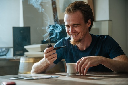Smiling young man smoke pipe, drink coffee, listen old music early morning and enjoy his life