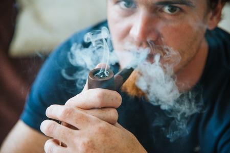 young redhead bearded man smoke pipe close-up