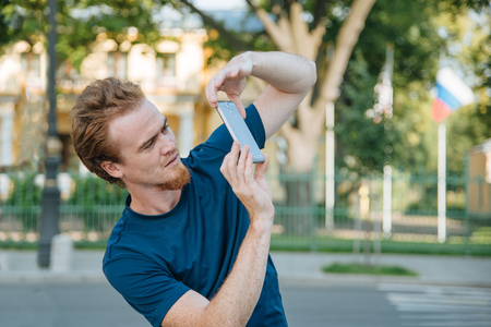 young man making photo and video on phone on the city street in summer day