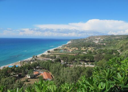 Panorama of the coast of Calabria on a hot sunny day. Lush greenery, blue sky, clouds, bright blue sea, strip of beaches.