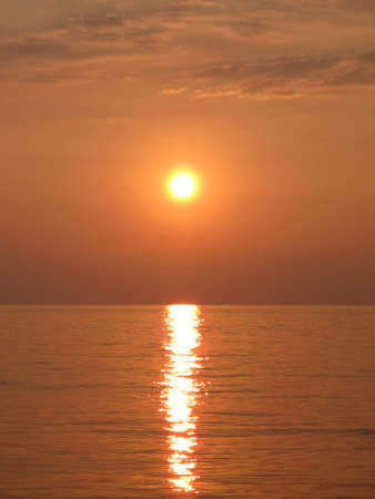 Scenic view of the bright golden setting sun and reflection in the sea water, sunset at the seaside, clouds, sky, sea and sun in bronze-orange-yellow tones