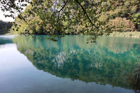 Wooded slope and sky reflected in the turquoise water of the lake, Plitvice Lakes National Park.Picturesque landscape of mountains and transparent calm lake, which reflects rocks, trees and sky