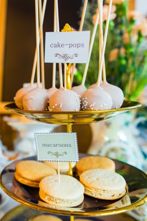 Macaroons and cake pops on wedding candy bar photo
