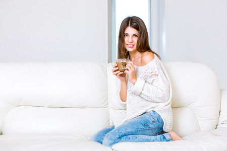 Cute girl on sofa with a cup photo