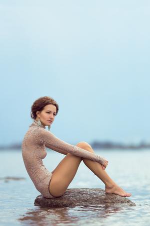 lonley: Sad skinny girl sitting on the stone Stock Photo