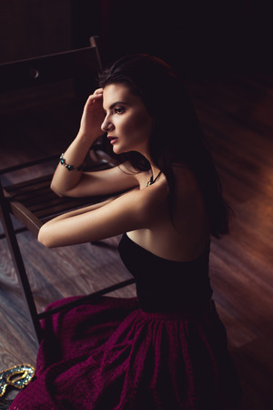 fitting in: young brunette model woman posing in fashionable clothes in burlesque fitting room