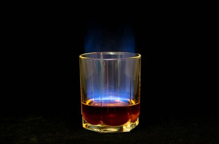 Alcoholic drink burns with a blue flame on a black background, whiskey.