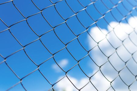 Metal fence close-up. The territory of the fence, against the sky.