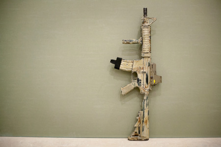 Assault Rifle, painted in sand color on a green background. Airsoft.