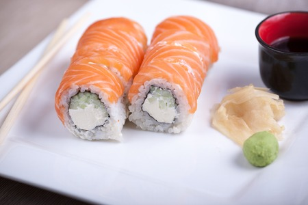 Philadelphia sushi roll with red fish on a white plate.