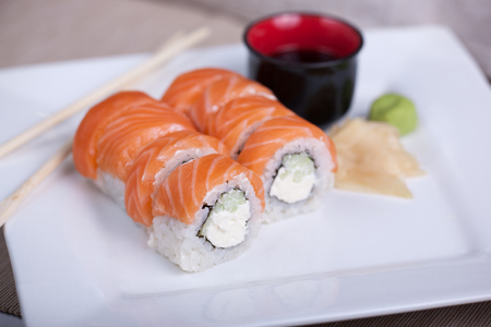 manjar: Philadelphia sushi roll with red fish on a white plate.