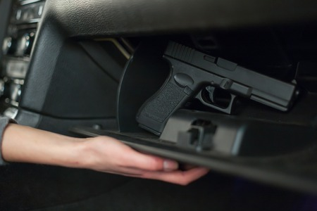 The female hand pulls out a gun from the glove box in the car