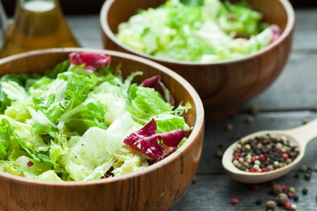 A dish of fresh salad frisse, Romano and radiccio with olive oil, salt and freshly ground percec in a wooden bowl.