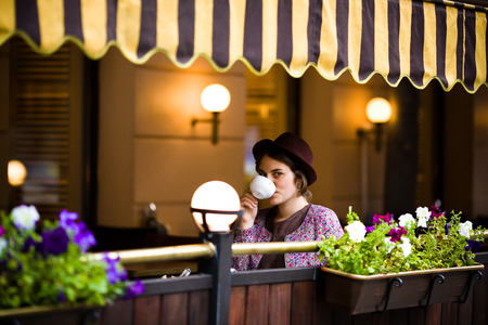 Beautiful young woman in a hat sits on a terrace in a cafe, drinks tea and looks at the camera.