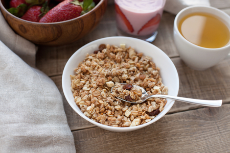 sunflower seeds: A bowl of homemade granola with yogurt and fresh strawberries on a wooden background. Healthy breakfast with green tea.