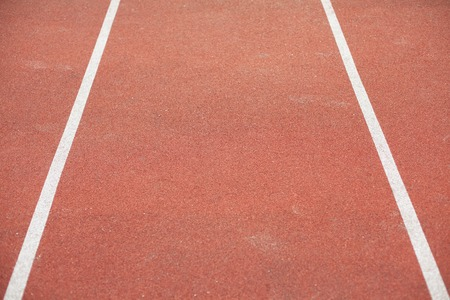 cushioned: white bent lines marking red stadium with soft covering.