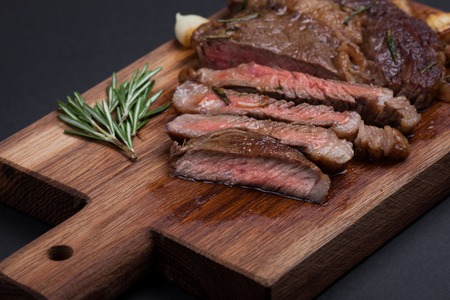 grafit: Grilled ribeye steak of marble beef closeup with spices on a wooden Board. Juicy steak medium sliced and ready to eat. With copy space. Top view