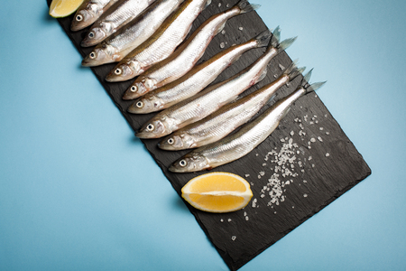Fresh sea fish smelt or sardines ready for cooking with lemon, thyme, and coarse sea salt on a blue background. The concept of fresh, healthy seafood. Top view.
