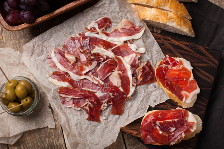 Jamon Iberico with white bread, olives on toothpicks and fruit on a wooden background. Top view.