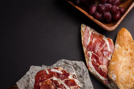 Jamon Iberico with white bread, olives on toothpicks and fruit on a dark background. Top view with copy space.