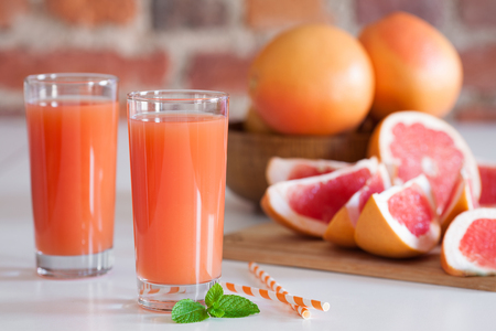Freshly pressed grapefruit juice with mint leaves on brick wall background closeup.