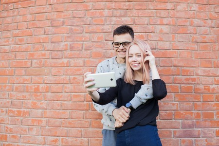 taking video: Young couple photographing a selfie with smartphone on the background of red brick wall.