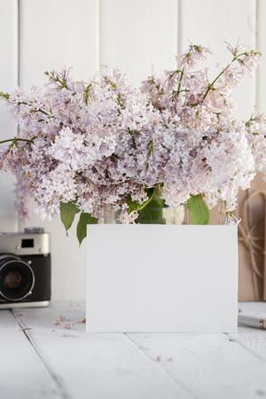 Lege witte groetkaart met lilac bloemenboeket en envelop met uitstekende camera op witte houten achtergrond. bespotten.