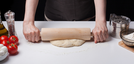 sprinkled: Female hand rolled pizza dough with a rolling pin on a white table, sprinkled with flour. Stock Photo