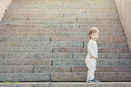 Little blue-eyed boy with long hair standing in front of the stone stairs. The concept of growing up.
