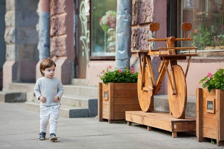Stylish, beautiful boy, three years old with long blond hair walks through the city.