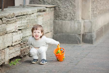 긴 금발 머리 울고 거리에 서있는 어린 소년. 그의 손에 그는 샌드 박스에서 놀기 위해 오렌지 양동이를 잡고있다. 위장이 아프다. 스톡 콘텐츠