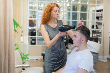 Male client getting haircut. Girl hairdresser dries my hair a young, attractive guy in a beauty salon. Stock Photo