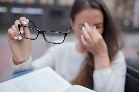 Closeup portrait of attractive female with eyeglasses in hand. Poor young girl has issues with vision. She rubs her nose and eyes out of fatigue. A student tired to study and read books.