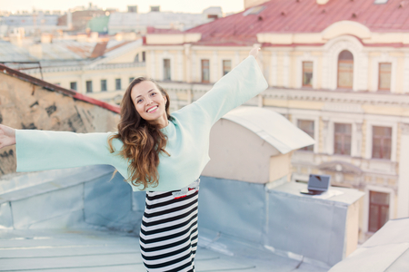 Portrait of a beautiful young girl who walks in the evening on the roofs of the old town. The concept of freedom. She stands with arms to the sides hands.